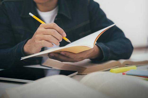 ノートに書くペンで手を閉じます。教育コンセプト。