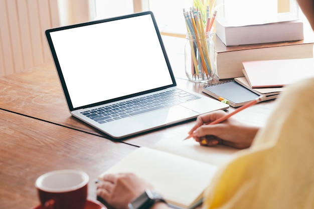 コンピューターを使用して、自宅で書く若い女性