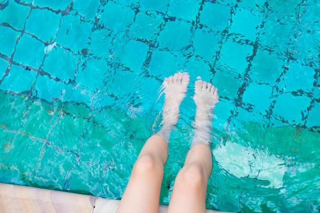 プールで水で足をリラックスさせる少女。