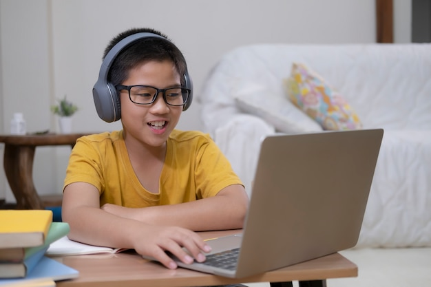 Молодой студент используя компьютер изучая онлайн.