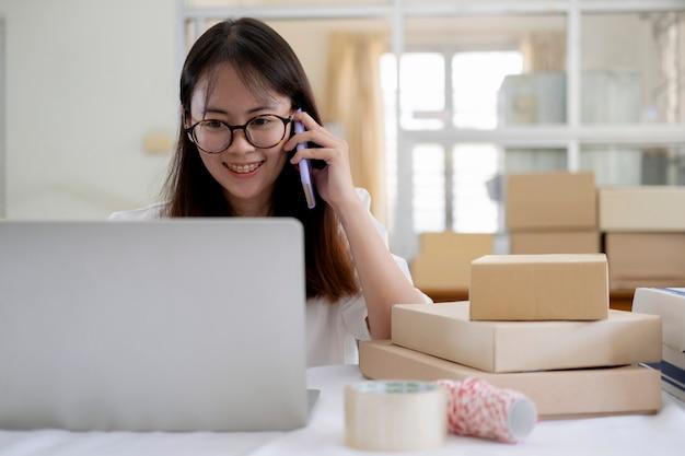 顧客からの注文を受け取って確認するために電話で話している若いオンライン販売者