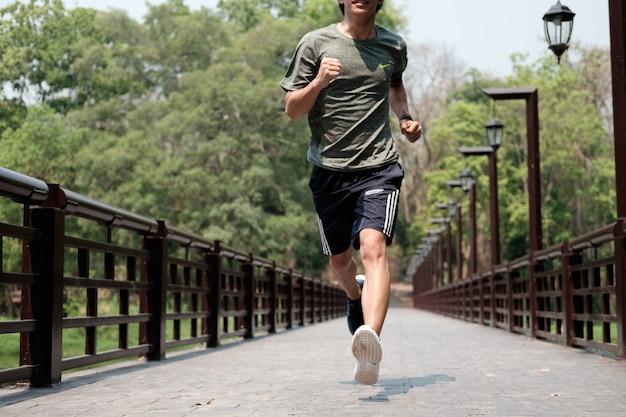 ランナーの男。健康とフィットネスのアウトドアコンセプト。男は朝にジョギングしている。若い、スポーツ、ジョギング、公園で。