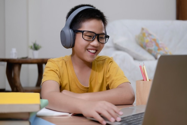 Азиатский мальчик наслаждается самообучением с помощью электронного обучения дома