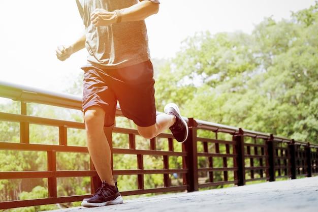 Молодой человек делает спорт и бег трусцой, в парке.