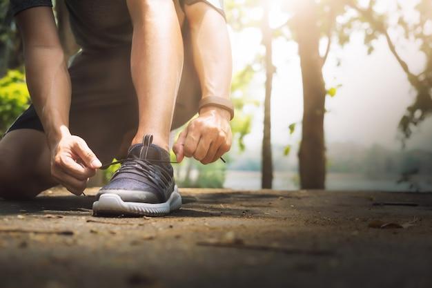 若い男ランナーは靴ひもを結ぶ。