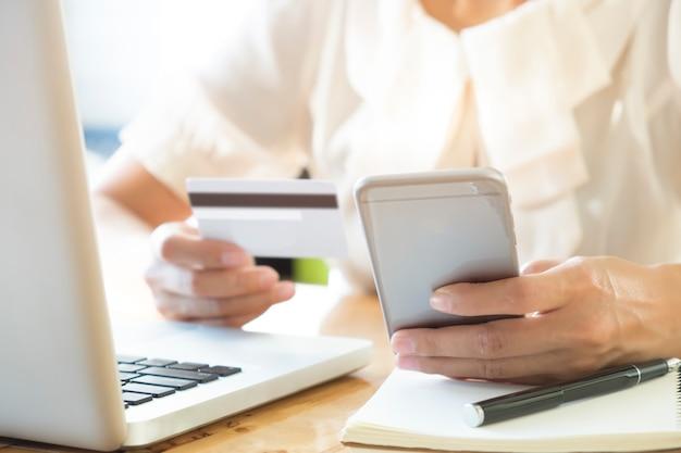 Женщина, держащая мобильный телефон и кредитную карту на ноутбуке для покупок в интернете