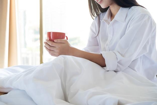 ベッドに座っている間、彼女のコーヒーを楽しむリラックスした若い女性。