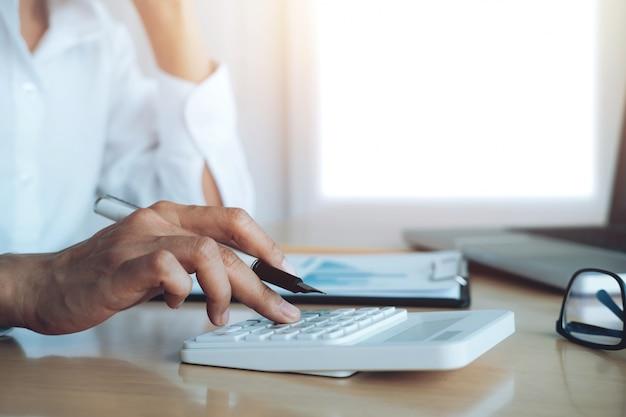 財政節約経済概念。女性の会計士または銀行家は電卓を使用します。