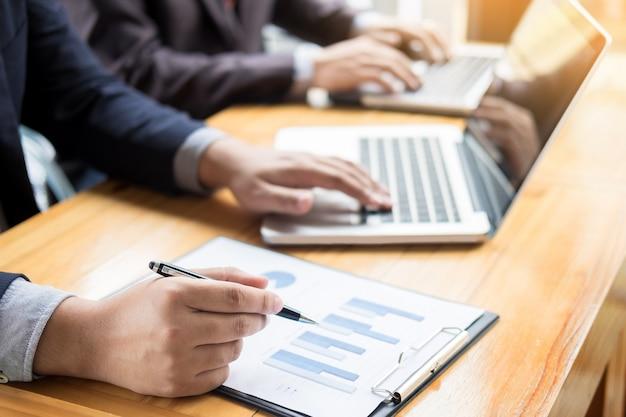 ビジネスマンは、彼のオフィスで利益財務データグラフの文書のレポートを分析しました。