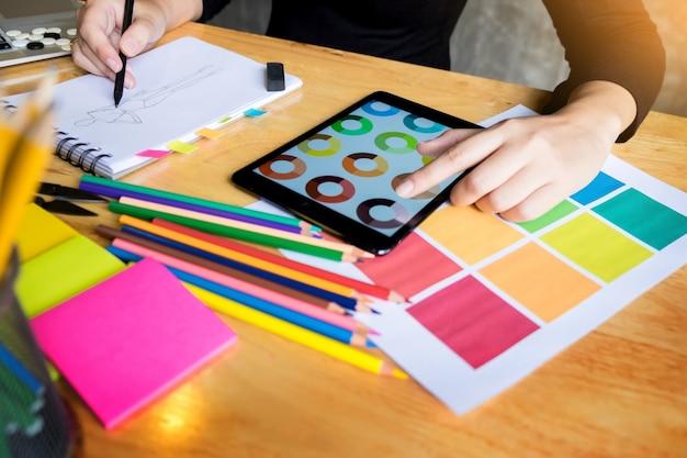Мужчины, работающие модельером, выбирающие на диаграмме цвета одежду в цифровом планшете на студии на рабочем месте.