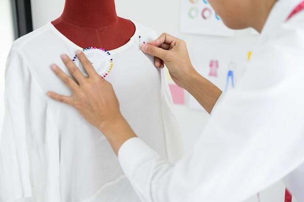 アジアのテーラーは、ワークショップでのマネキンの衣服デザインを調整して、スタジオのモデルで作業を少し調整します。