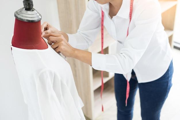 アジアの仕立て屋は、ワークショップでマネキンの縫製デザインを調整します。