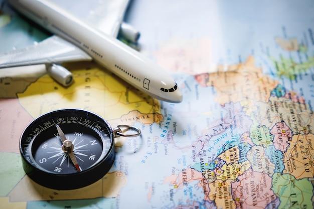 Селективный фокус миниатюрного туриста на компасе над картой с пластиковым игрушечным самолетом, абстрактным фоном для концепции путешествия.