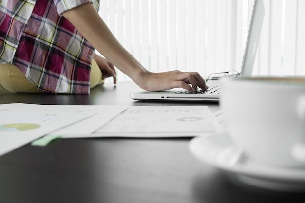 Деловой человек, сидя за столом и набрав на ноутбуке