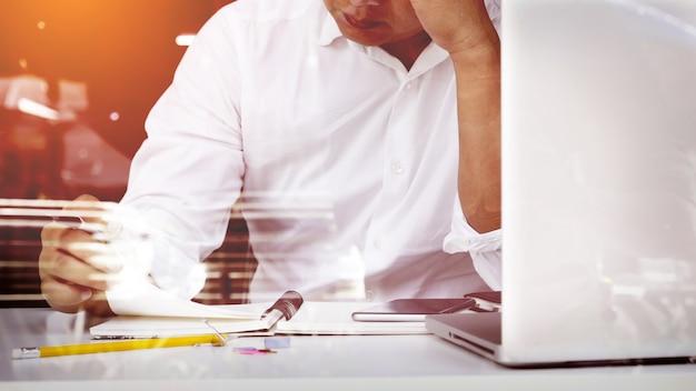 ビジネスマン、報告書を見て自宅のオフィススペースに座っています。
