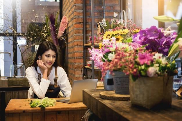 ラップトップを探している女性の花屋は彼女の花屋のカウンターで注文を受けた