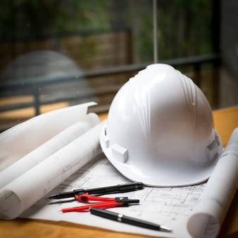 建設コンセプトイメージヘルメットは、レトロスタイルの木製ボード上に青写真を巻いた。