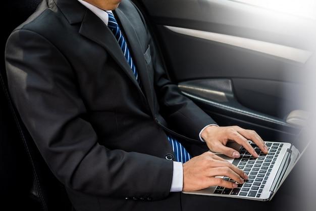 Красивый молодой предприниматель, используя ноутбук и сидя на заднем сиденье автомобиля.