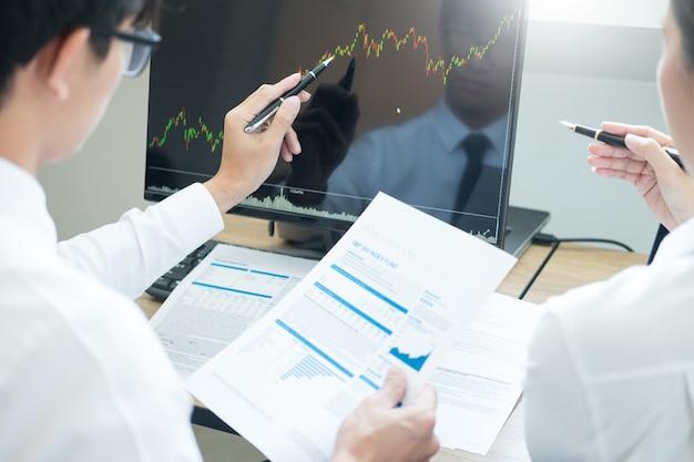 チーム投資起業家のコンピューター上での取引チャートとグラフの議論と分析