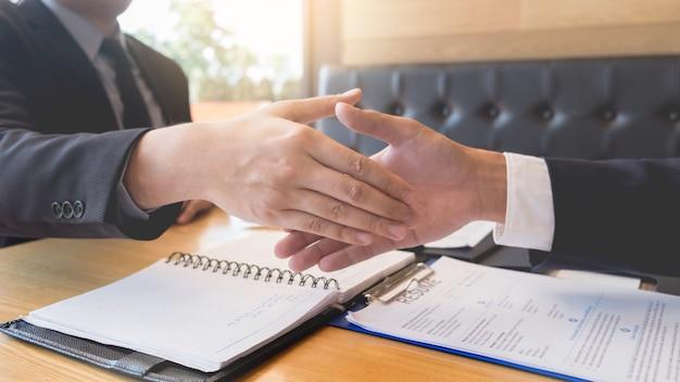 交渉または面接が成功した後のビジネス上司および従業員のハンドシェイク。