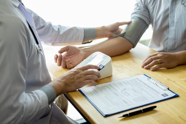 医者測定し、病院、ヘルスケアの概念で患者の血圧をチェックします。
