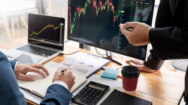 証券会社のチームディスプレイ画面での議論投資のための株式市場取引のデータ、グラフ、レポートの分析