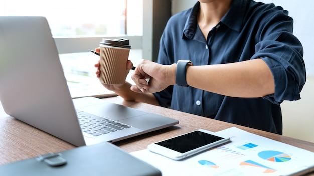 ビジネスの男性のラップトップでグラフデータとオフィスで彼の机の上のドキュメントを操作します。
