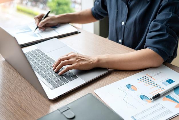 Бизнесмен работая с данными по диаграммы в компьтер-книжке и документами на его столе на офисе.