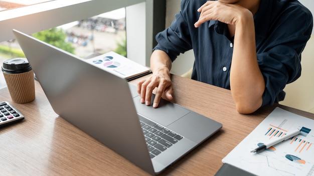 ビジネスの男性は、オフィスで彼の机の上のノートパソコンとドキュメントのグラフデータを操作します。