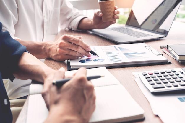 ビジネスマンは、現代のオフィスで一緒に同僚の同僚またはパートナーとドキュメントで新しいトレンド情報を説明することについて話し合います。