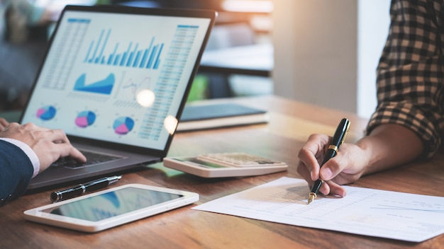 ビジネスの創造的な同僚チーム会議チャートとグラフの仕事を議論します。