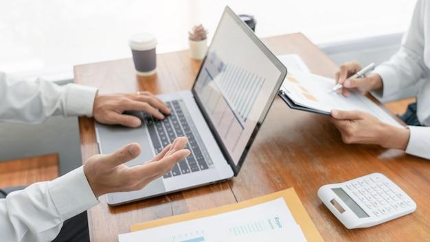 Бизнесмены говоря обсуждающ с планированием сотрудника анализируя диаграммы и диаграммы данным по финансового документа в встрече и успешной концепции сыгранности.