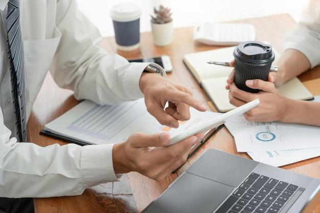 金融文書のデータチャートを分析する同僚の計画と議論