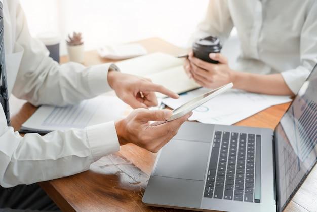 Говорящие деловые люди обсуждают с коллегами по планированию, анализируя диаграммы данных финансового документа