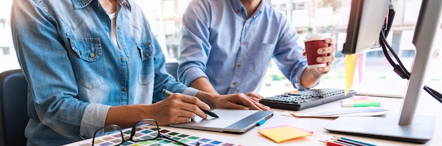 Дизайнер графического творчества творчества совместной работы окраски с помощью графического планшета и стилуса на столе с коллегой.