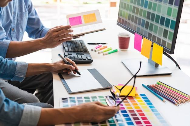 グラフィックタブレットとスタイラスを使用して一緒に着色するデザイナーグラフィッククリエイティブな創造性