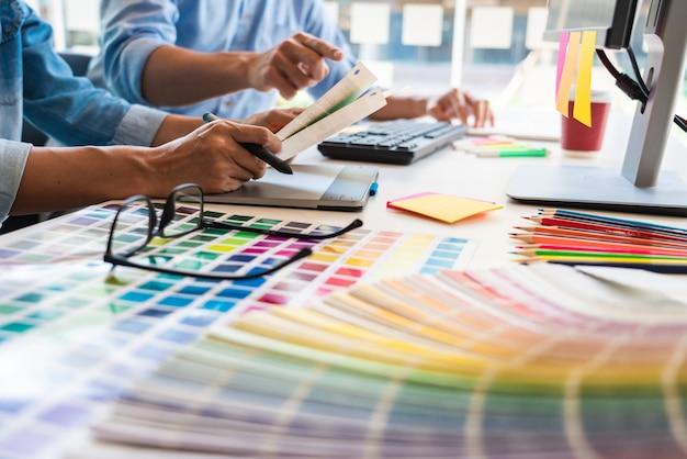 オフィスのデスクトップコンピューターのプロジェクトのカラーパレットのサンプルを選択するプロの創造的な建築家グラフィックデザイン職