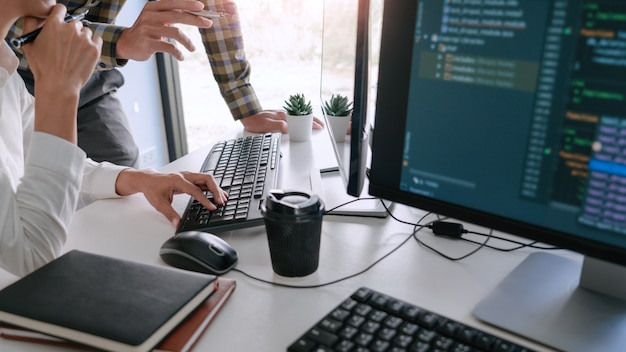 Молодые стартаперы-программисты, сидящие за столами и работающие на компьютере, открывают окно для разработки программ и кодирования, чтобы найти решение проблемы в новом приложении