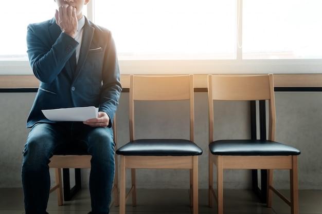 椅子の列に不安な、面接のための待合室で若い実業家。