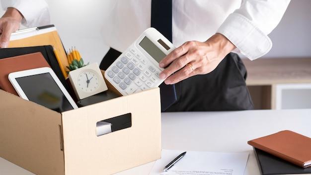 ビジネスマンが辞任文書を保持していると茶色の段ボール箱に個人の会社を梱包