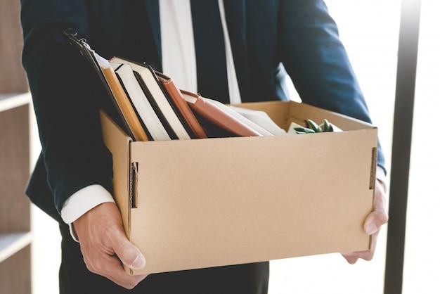 ビジネスマンは鉢植えやドキュメントを含むボックスを保持します
