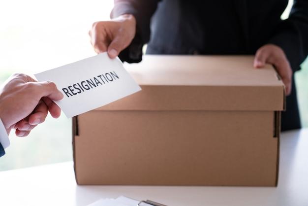 ビジネスマンは、契約、仕事の配置および空席の概念を却下するために辞任するために机の上の幹部雇用主の上司に辞表を送る。