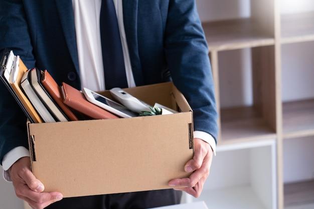 悲しい解雇の若い従業員のビジネスマンは、鉢植えや個人の持ち物失業、辞任されたコンセプトのドキュメントなどのボックスを保持しています。