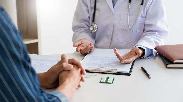 Пациент внимательно прислушивается к врачу-мужчине, объясняющему симптомы пациента или задающему вопрос, когда они вместе обсуждают документы на консультации