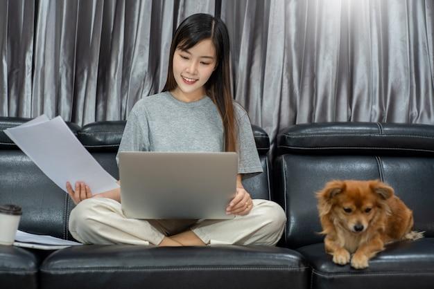 Красивая молодая азиатская женщина работая удаленно от дома и усмехаясь пока лежащ, имеет хорошие отношения с с смешным ассистентским любимчиком собаки, концепцией любимчиков домашней работы.