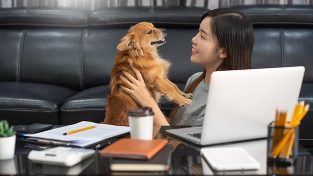 Молодая красивая азиатская женщина работая дома с ее любимчиком