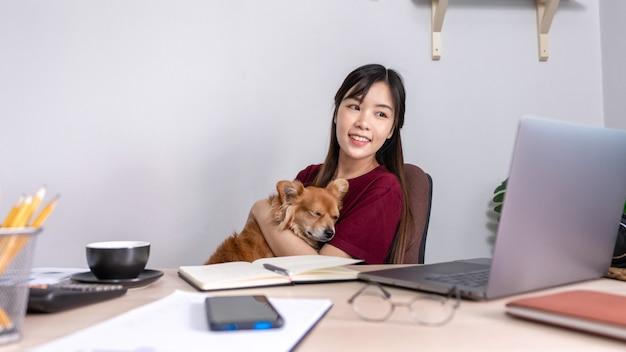 Молодая красивая азиатская женщина работая дома с ее собакой