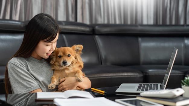 Довольно азиатская женщина работая удаленно от дома используя компьтер-книжку сидя на кресле или софе в живущей комнате для работы онлайн с собакой щенка любимчика милой и попечителем, концепцией баланса жизни работы.