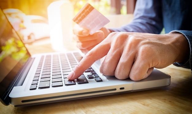 手にクレジットカードを持っていて、ノートパソコンのキーボードを使ってセキュリティコードを入力している男