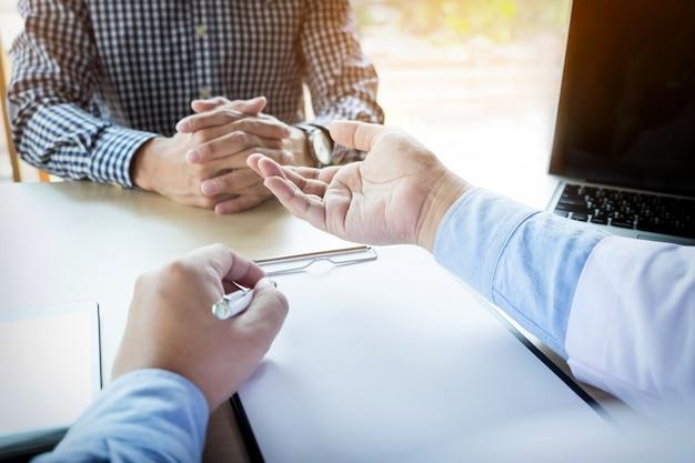 患者は患者の症状を説明する男性医師に熱心に耳を傾け、相談で書類を一緒に話し合って質問する